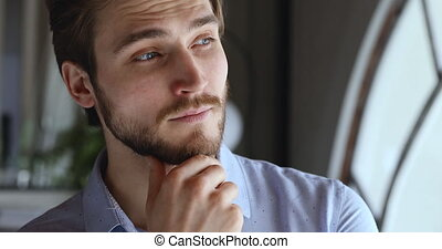 Worried thoughtful young businessman looking away thinking of future business challenges due financial crisis. Doubtful serious entrepreneur lost in thoughts considering risks, opportunities. Close up