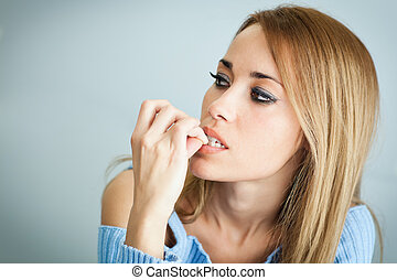 portrait of 30 years old woman biting her fingernails on cyan background. Horizontal shape, Copy space