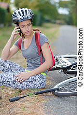 worried woman calling for help after falling from bicycle