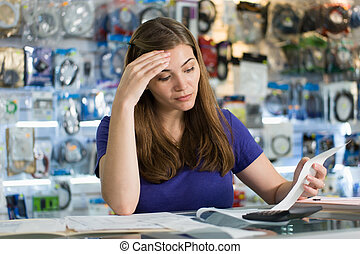 Worried Woman Checking Bills And Invoices In Computer Shop...