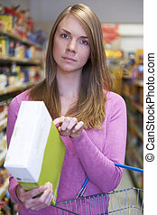 Worried Woman Checking Contents Of Box In Supermarket