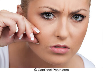 Worried woman. Displeased young woman touching her face while isolated on white