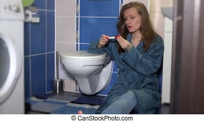 Worried woman looking at a pregnancy test in the bathroom.