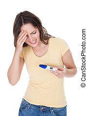 Worried Woman Looking At Pregnancy Result