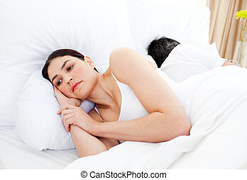 Worried woman lying in her bed separately from her husband