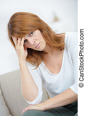 Worried woman sat with head in hands