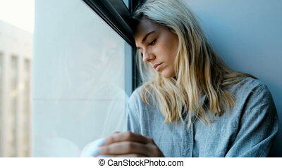 Worried woman sitting near window 4k - Worried woman sitting...