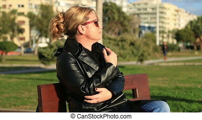 Worried woman sitting on a park ben