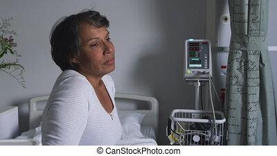Worried woman sitting on hospital bed 4k - Waist up handheld...