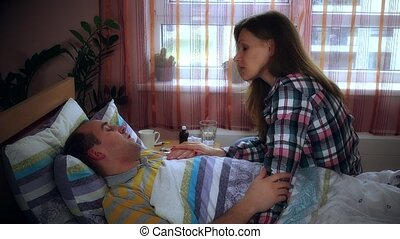 Worried woman talking with sick ill man lying in bed and coughing