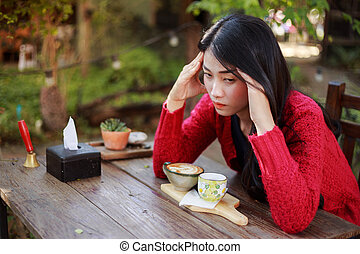 worried woman with a cup of coffee in the garden