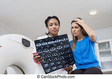 Worried Woman With Doctor Looking At CT Scan Chest X-ray