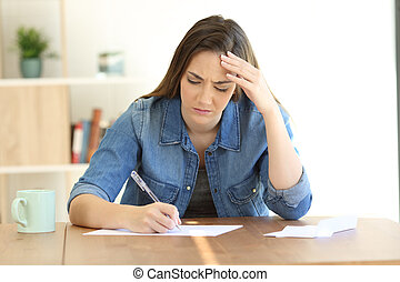 Worried woman writing a letter at home