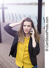 Worried young businesswoman using mobile phone outdoor