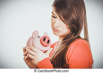 Worried young woman with piggybank.