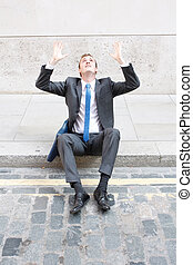 Worries - A worried business man sitting on some stairs