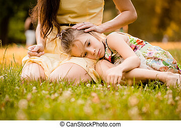 Worries of childhood - Mother is caressing her worried child...