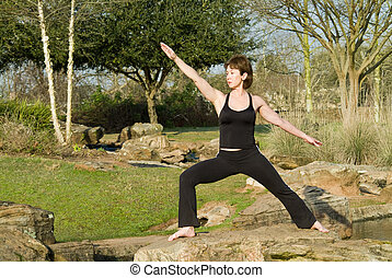 A woman standing on a rock in a yoga posture called warrior pose.