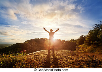 Worship and praise - Silhouette of a man with hands raised...
