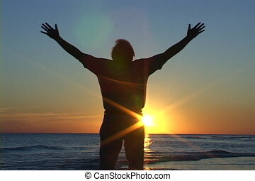 Worship At Sunset - Mature man with hands raised, rejoices...