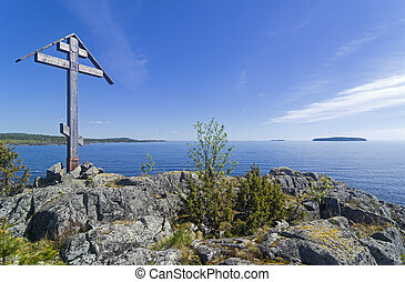 Worship cross on a rock on the shore of the Ladoga Lake