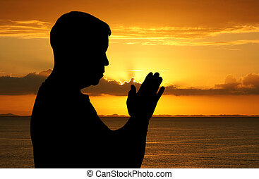 Worship - Man praying with his hands folded at sunset