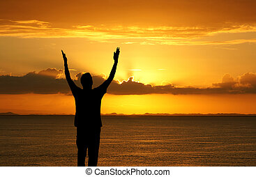 Worship - Man with his hands up watching the sun set
