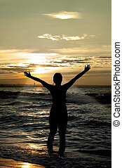 worshipper against incredible summer sunset on the beach, person isn't identifable