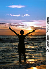 worshipper against incredible summer sunset on the beach