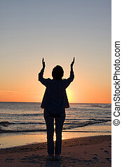 Woman raises her hands toward heaven in praise and worship. Room for copy at top.