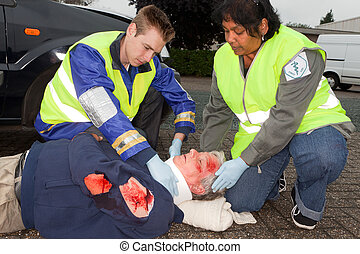 Wounded man and paramedics helping him with a neck brace (the sleeve badges have been replaced by a non existing logo)