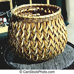 WOVEN BASKET - A woven basket sits atop a barrel