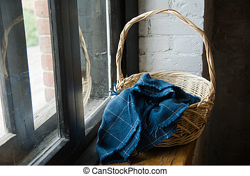 Woven basket covered with a blue cloth of soty on the windowsill