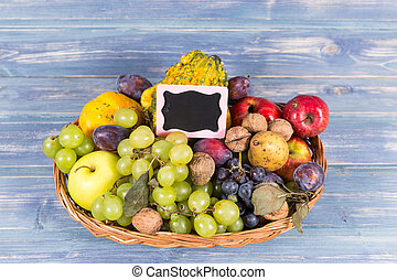 Woven basket full of autumn fruits and small chalkboard