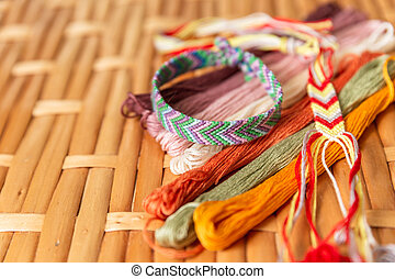 Woven bracelet made of bright threads, colorful threads for embroidery on a rattan table. Hobbies, jewelry in the style of boho, hippies. Handmade