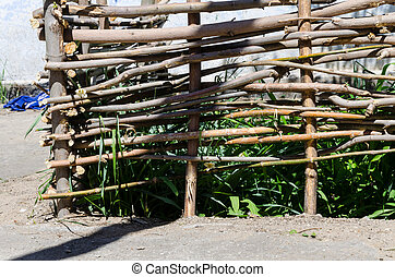 Woven wooden fence made of thin old twigs