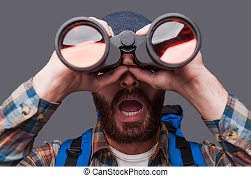 Wow! Surprised young bearded man carrying backpack and looking through binoculars while standing against grey background