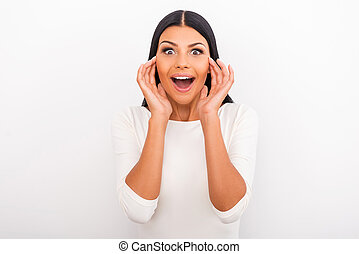 Wow! Surprised young woman keeping mouth opened and holding hands near her face while standing against white background
