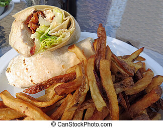 Wrap and Fries Closeup - A chicken Caesar wrap served with...