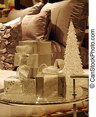 Wrapped Christmas gifts on a glass table next to the bed (...