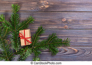 Wrapped Christmas gifts on dark rustic wooden table fir branches. With copy space for your text
