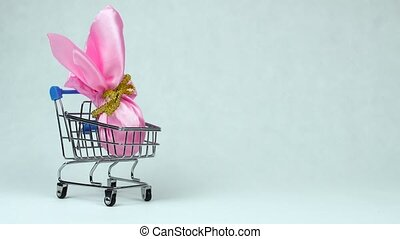 Wrapped Easter egg is placed into the toy shopping cart...