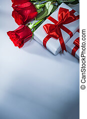Wrapped gift boxes natural roses on white background