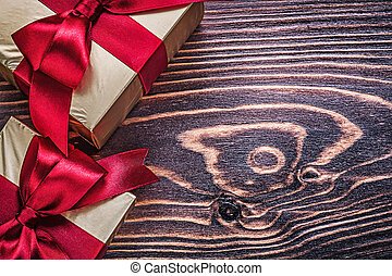 Wrapped gift boxes with red satin ribbons on wood board.
