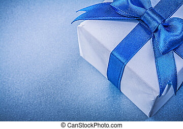 Wrapped present box with bow on blue background