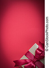 Wrapped present on red background vertical view holidays concept