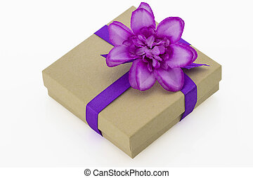 Wrapped vintage gift box with purple ribbon and flower isolated
