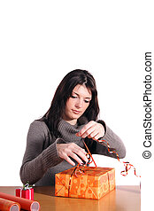 A handsome young woman wrapping presents. All isolated on white background.