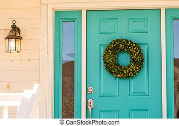 Green wreath decorating front door.