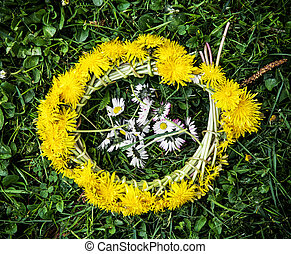 Wreath of dandelions with ox-eye daisies in the green grass